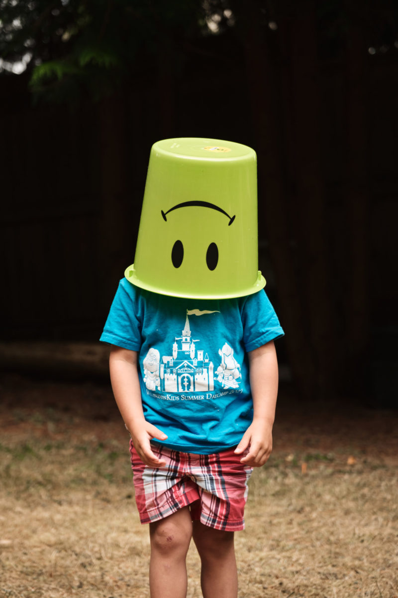 Photo of child with bucket on their head
