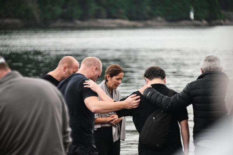 Photo of people praying at a baptism